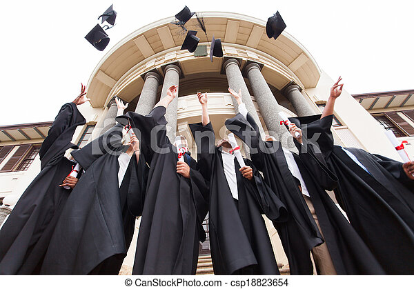 group of graduates throwing graduation hats in the air - csp18823654