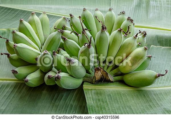 group of green banana on banana leaf background - csp40315596