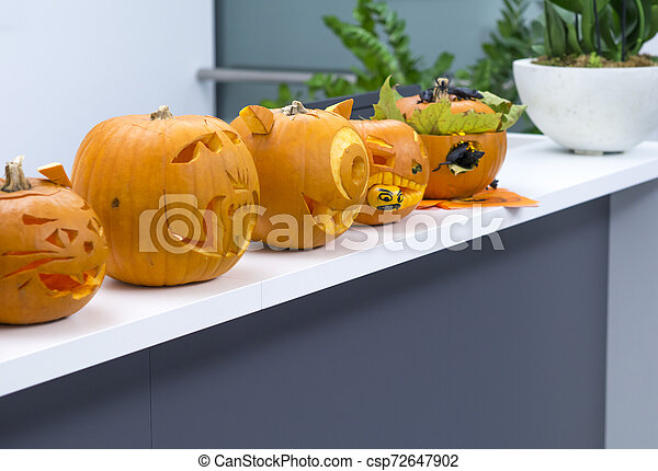 Group of Halloween big orange pumpkin decorated with scary face. Jack O' Lantern on white table background - csp72647902