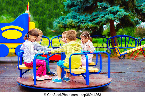 group of happy kids having fun on roundabout at playground - csp36944363