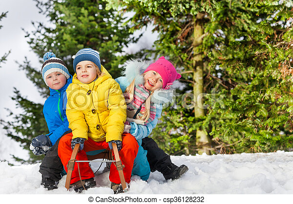Group of little children slide on sledge in park - csp36128232