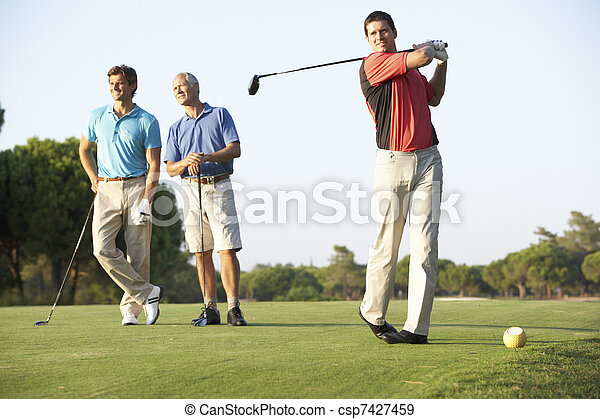 Group Of Male Golfers Teeing Off On Golf Course - csp7427459