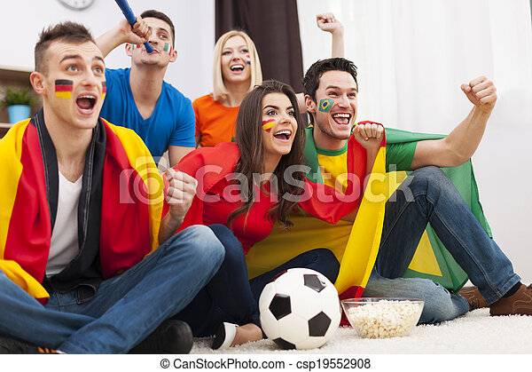 Group of multinational people cheering football match at home  - csp19552908