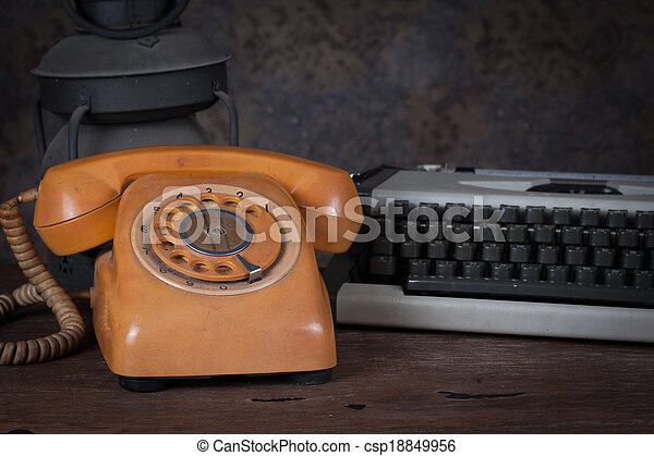 Group of objects on wood table. old telephone, type writer, old rusty kerosene lamp, Still life - csp18849956