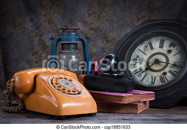 Group of objects on wood table. old telephone, type writer, old camera, Still life - csp18851633