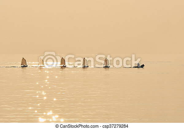 Group of Optimist sails towed into port bu rubber boat - csp37279284