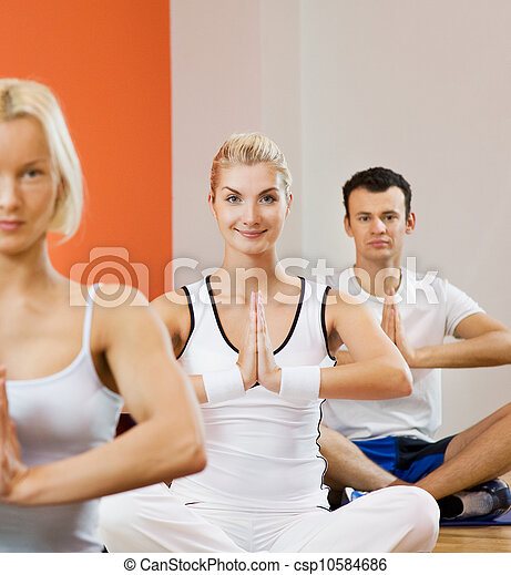 group of people doing yoga exercise focus on a woman in