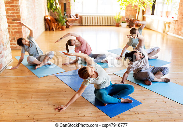 group of people doing yoga exercises at studio fitness