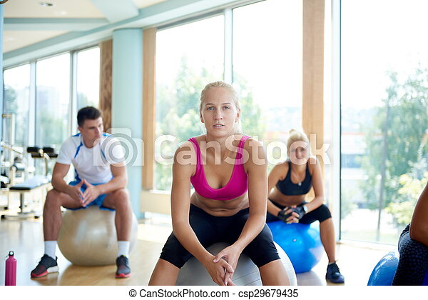 group of people exercise with balls on yoga class in
