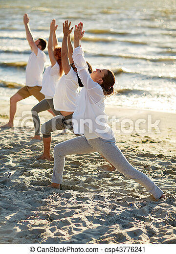 group of people making yoga exercises on beach fitness