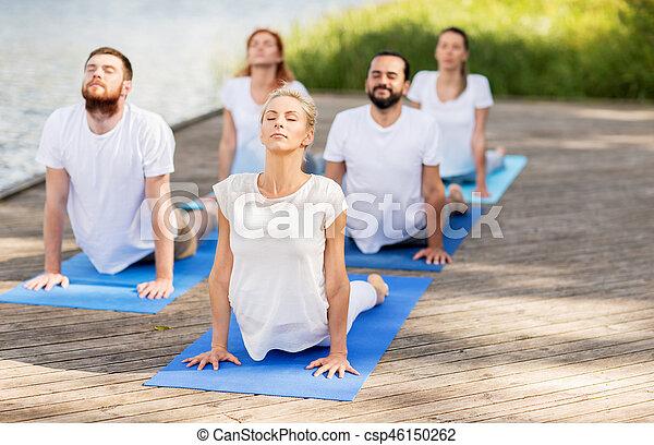 group of people making yoga exercises outdoors yoga