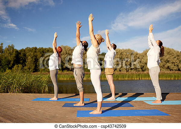 group of people making yoga exercises outdoors fitness