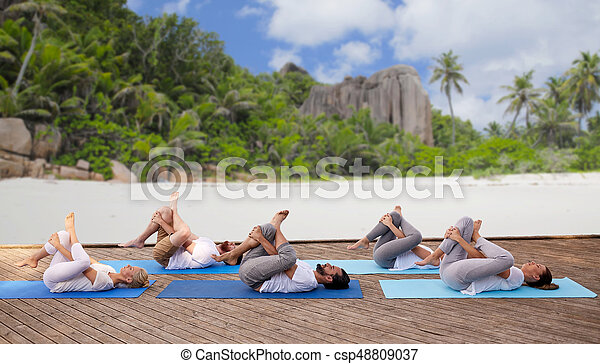 group of people making yoga exercises over beach fitness