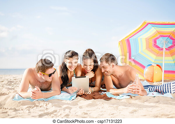 group of smiling people with tablet pc on beach - csp17131223