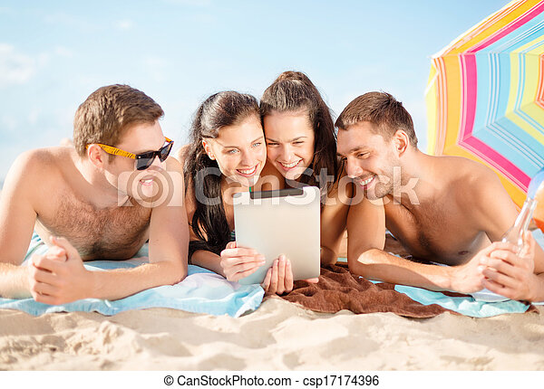 group of smiling people with tablet pc on beach - csp17174396