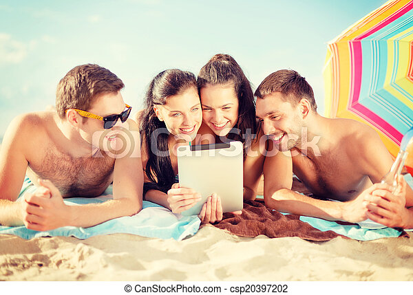 group of smiling people with tablet pc on beach - csp20397202
