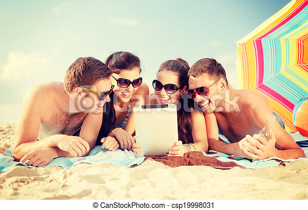 group of smiling people with tablet pc on beach - csp19998031