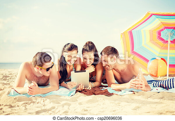 group of smiling people with tablet pc on beach - csp20696036