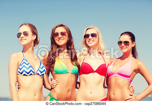 group of smiling young women on beach - csp27586044