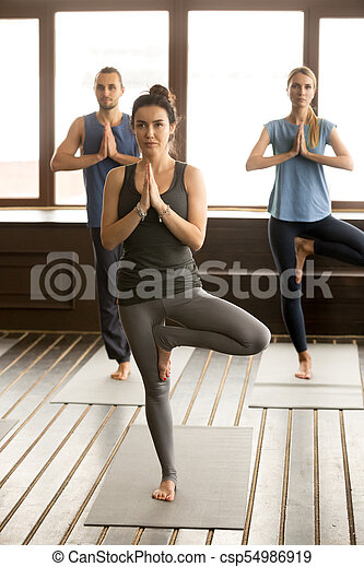 group of sporty people in tree pose group of three young
