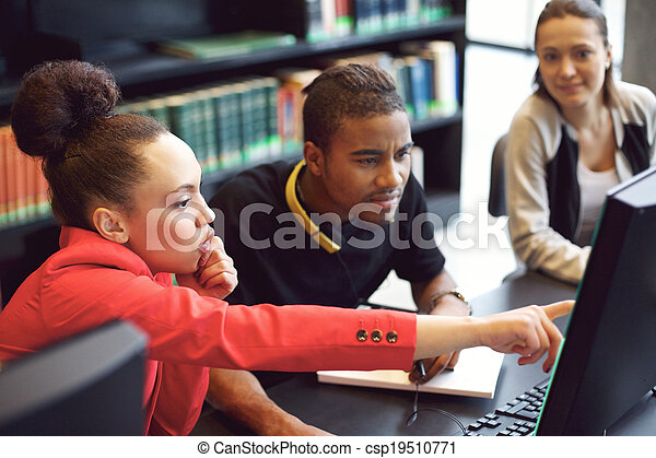 Group of students doing online research in library - csp19510771