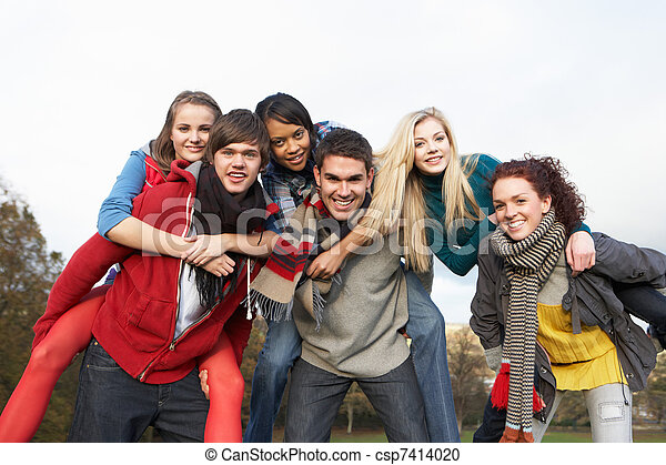 Group Of Teenage Friends Having Piggyback Rides In Autumn Landscape - csp7414020