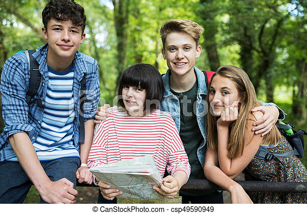 Group Of Teenage Friends Hiking In Countryside Together - csp49590949