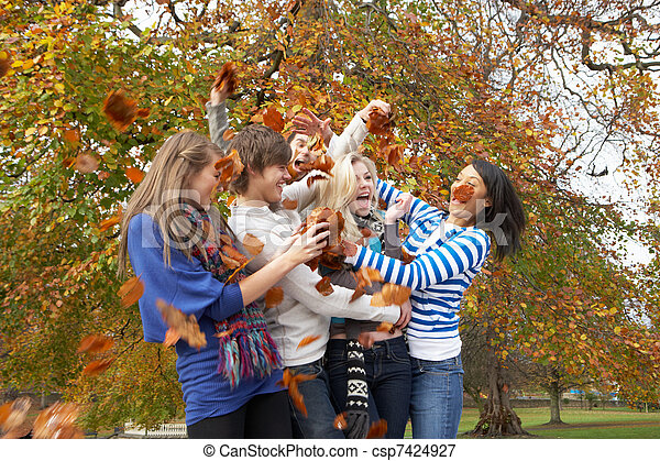 Group Of Teenage Friends Throwing Leaves In Autumn Landscape - csp7424927