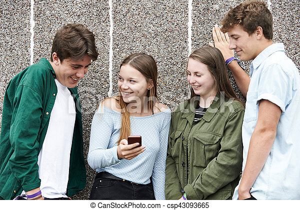 Group Of Teenagers Looking At Text Message On Mobile Phone - csp43093665