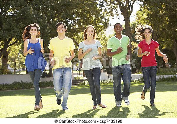 Group Of Teenagers Running Through Park - csp7433198