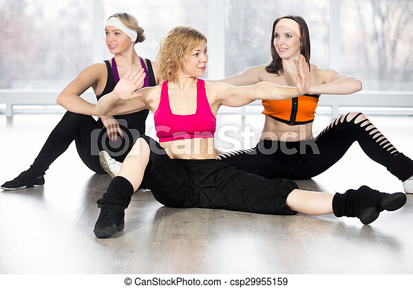 Group of three females doing dynamic fitness exercises in class - csp29955159