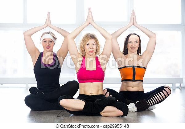 group of three yogi females sitting in easy pose sporty