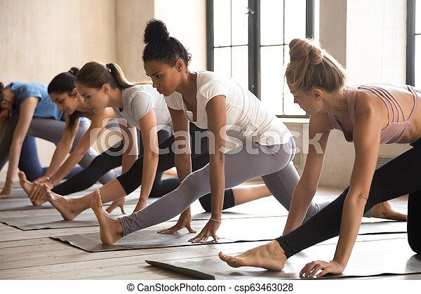 group of women practicing yoga lesson doing half splits