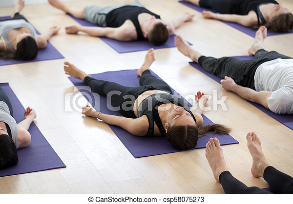 group of young sporty people in corpse pose group of