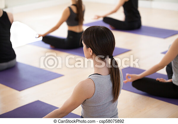 group of young sporty people in sukhasana pose close up