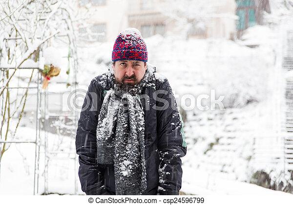 Grumpy man in a snowy garden - csp24596799