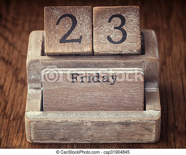 Grunge calendar showing Friday the twenty third on wood background - csp31904845