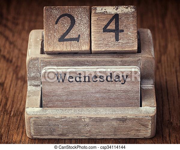 Grunge calendar showing Wednesday the twenty fourth on wood background - csp34114144