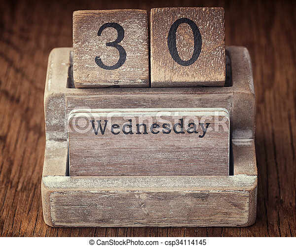 Grunge calendar showing Wednesday the thirtieth on wood background - csp34114145