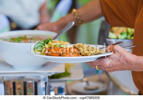 La gente organiza comida de buffet en un restaurante de lujo con frutas color carne y verduras - csp47989309