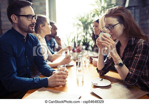 Grupo de gente feliz de negocios comiendo en un restaurante - csp54648329
