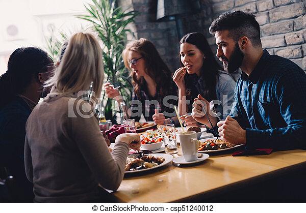 Grupo de gente feliz de negocios comiendo en un restaurante - csp51240012