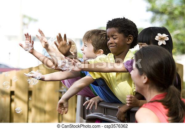 Un grupo de niños de 5 años jugando en la guardería con el profesor - csp3576362