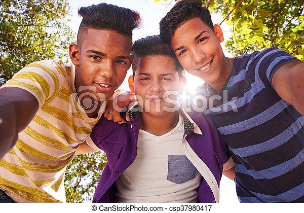Grupo Multiténico de adolescentes abrazando sonriendo a la cámara - csp37980417