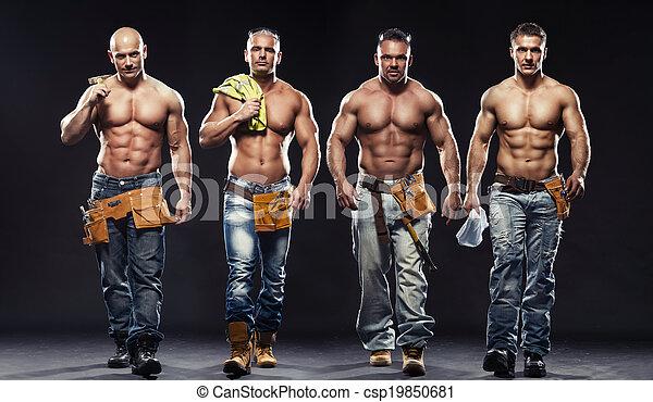 Eine Gruppe junger, gutaussehender Bauarbeiter, die auf dunklem Hintergrund posieren - csp19850681