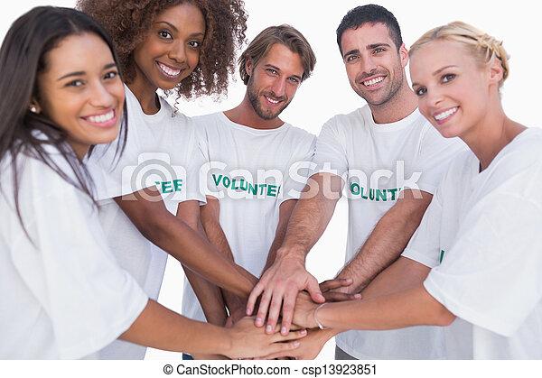 Eine lächelnde Freiwilligengruppe, die Hände zusammenlegt - csp13923851
