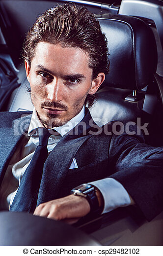 Un hombre apuesto con barba en un auto de traje - csp29482102