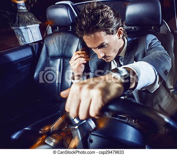 Un hombre apuesto con barba en un auto de traje - csp29479633