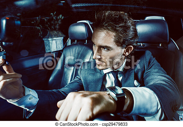 Un hombre apuesto con barba en un auto de traje - csp29479833