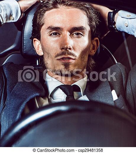 Un hombre apuesto con barba en un auto de traje - csp29481358